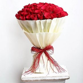 100 red roses wrapped with white paper and tied with red threads
