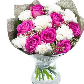 Pink roses and white carnation in a glass vase