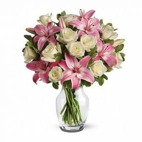 Pink lilies and white roses in round glass vase