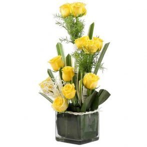 12 yellow roses decorated with green leaves in a square glass vase
