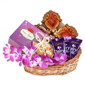 Basket of purple orchids, diary milk and soan papdi with diyas