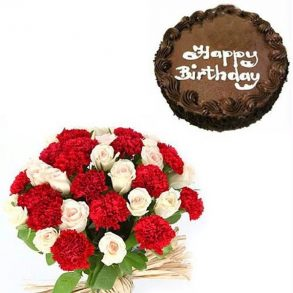 Round shaped chocolate cake and bunch of red carnation and white roses