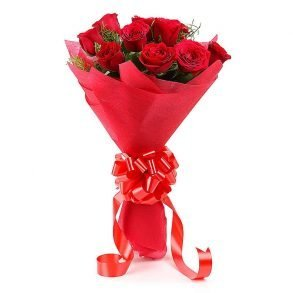 12 red roses with green leaves wrapped in red paper and tied with red ribbon
