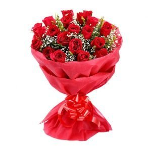 red roses with green leaves wrapped in red paper and tied with red ribbon