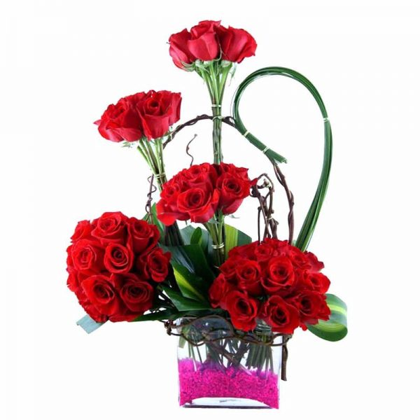 Red roses and seasonal green leaves in a square glass vase