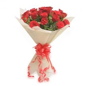 Red roses wrapped with white paper and tied with red ribbon