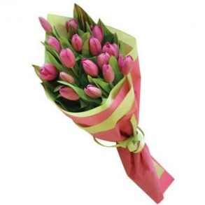 Pink tulips wrapped with pink and yellow paper and tied with yellow ribbon