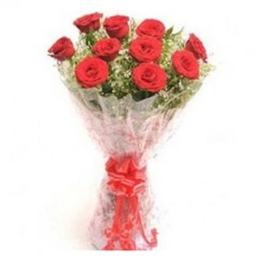 Red roses and seasonal leaves wrapped with cellophane and tied with red ribbon