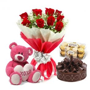 Red roses and seasonal green leaves, and round shaped chocolate cake with chocolates and pink teddy