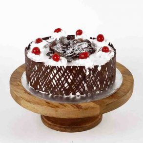 Round shaped black forest cake decorated with chocolate crust and cherries