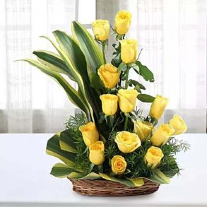 15 yellow roses decorated with green leaves in a basket