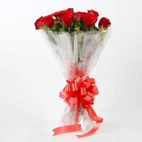 10 red roses with seasonal green leave wrapped in cellophane and tied with red ribbon