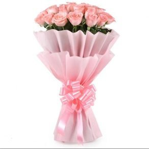 25 light pink roses with green leaves wrapped in pink paper and tied with pink ribbon