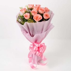 10 light pink roses with green leaves wrapped in pink paper and tied with pink ribbon