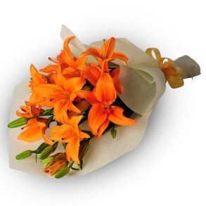 Orange lilies wrapped in off white paper and tied with ribbon