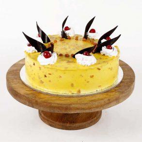 Round shape yellow pineapple cake decorated with cream, chocolate and cherries