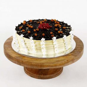 Spiral design round shaped pineapple cake decorated wit chocolate syrup, butter scotch, and cherries