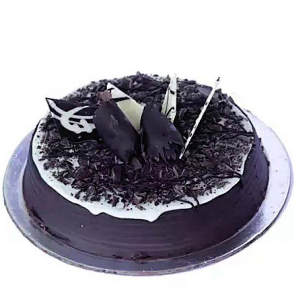 Round shaped chocolate cake decorated with white cream and chocolate crust.