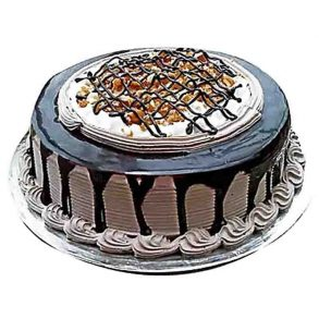 Round shaped chocolate cake decorated with chocolate syrup and dryfruits