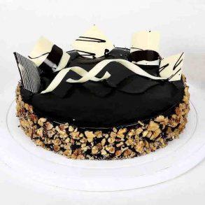 Round shaped chocolate walnut cake decorated with walnut and white & black chocolate crust