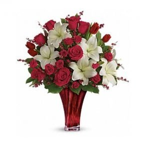 Red roses and white lilies in a red glass vase