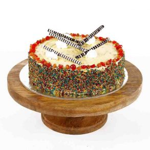 Round shaped pineapple cake decorated with colored vermicelli and cream with cherries on top