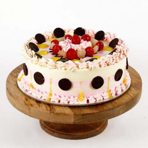 Designer rond shaped pineapple cake decorated with cream, cherries and brown chocolate coins on top and side
