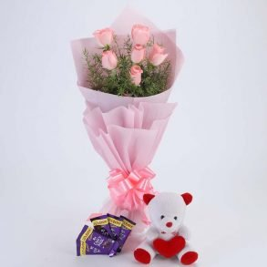 6 pink roses with green leaves wrapped in pink paper and tied with pink ribbon with 5 dairy milk and teddy