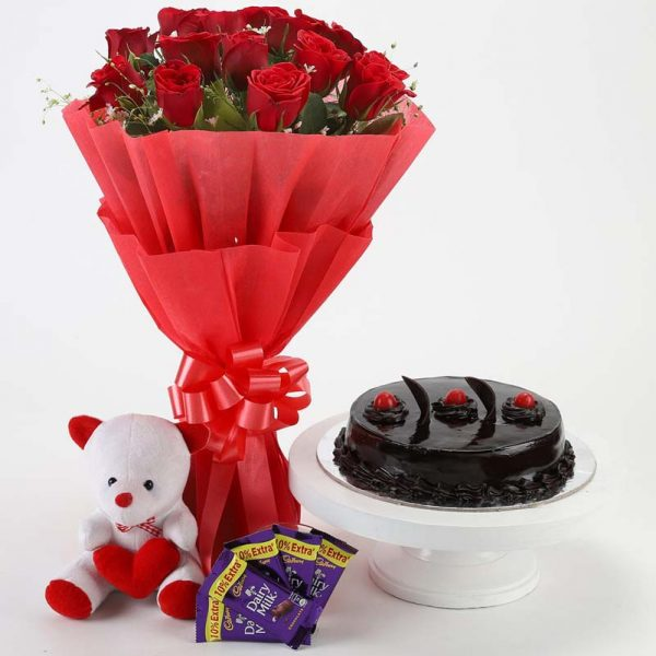 15 red roses wrapped in red paper and tied with red ribbon with half kg chocolate truffle cake, teddy and 5 dairy milk