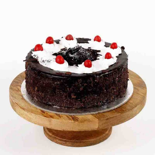 Round shaped black forest cake decorate with white creame and cherries