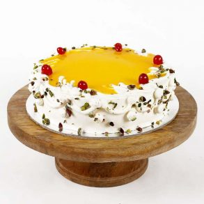 Round shaped pineapple cake decorated with yellow pineapple syrup and cherries on top, and pistachios on side
