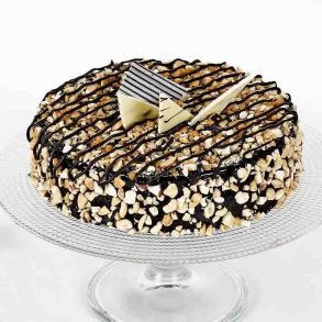 Round shaped chocolate cake decorated with dryfruits and white chocolate pieces
