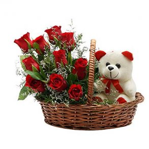 Basket of red roses and seasonal green leaves and white teddy
