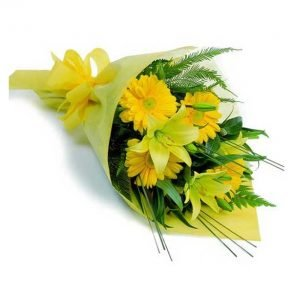 Yellow gerberas and yellow lilies with green leaves wrapped with yellow paper