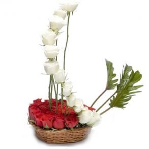 Basket of white and red roses decorated with green leaves