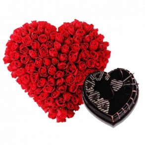 Heart shaped flower arrangement of red roses with heart shaped chocolate cake