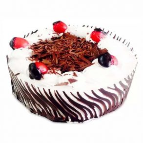 Round shaped black forest cake decorated with chocolate crust and red cherries