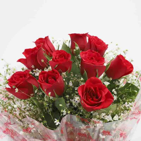 10 red roses with green leaves wrapped in cellophane