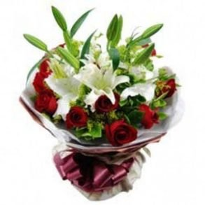 white lilies and red roses wrapped in white paper and tied with maroon ribbon