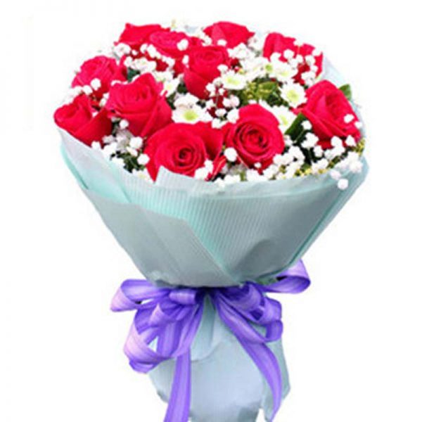 red roses with seasonal small white flowers wrapped in blue paper and tied with purple ribbon