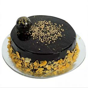 Round shaped chocolate cake decorated with golden pearls
