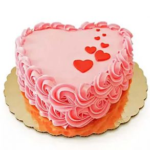 Heart shaped chocolate cake decorated with pink cream and red hearts on top
