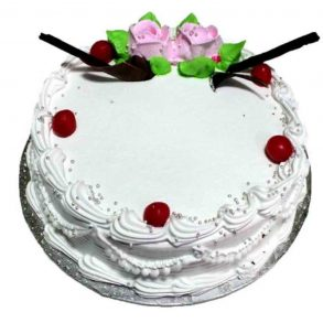 Round shaped vanilla cake with red cherries on top
