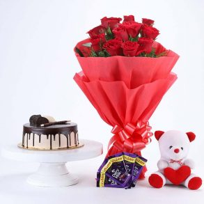 12 red roses wrapped in red paper and tied with red ribbon with half kg chocolate cake, teddy and 5 dairy milk
