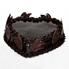 Heart shaped dark chocolate cake decorated with chocolates on side