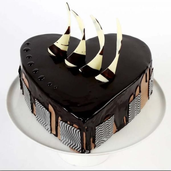 Heart shaped chocolate cake decorated with dark chocolate syrup and white and brown chocolate stick on top