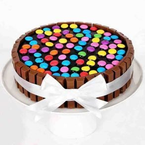 Round shaped kitkat cake decorated with kitkat on side and gems on top