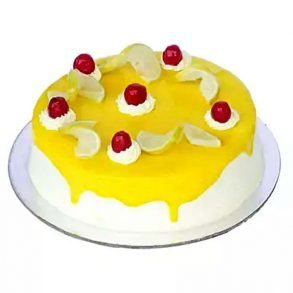 Round shaped lemon vanilla cake decorated with lemon slices and red cherries