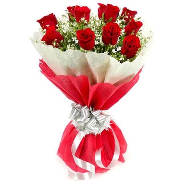 Red roses and seasonal green leaves wrapped with red and white paper and silver ribbon