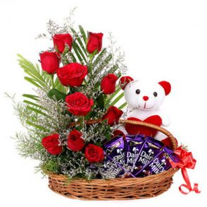 Basket of red roses with seasonal green leaves, and dairy milk chocolates with small teddy